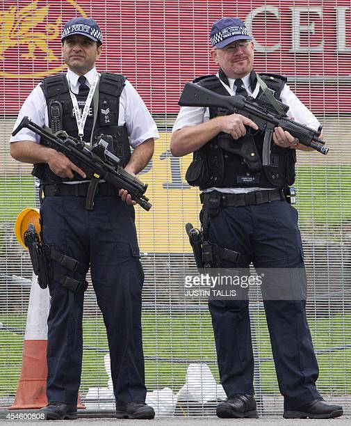 Armed police officers stand guard outside the Celtic Manor Resort the venue hosting the NATO 2014 summit in Newport south Wales on September 4 2014...
