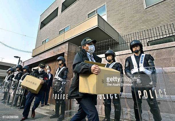 Armed police officers stand guard while other officers leaves with seized boxes after the raid at the Kobe Yamaguchigumi headquarters on suspicion of...
