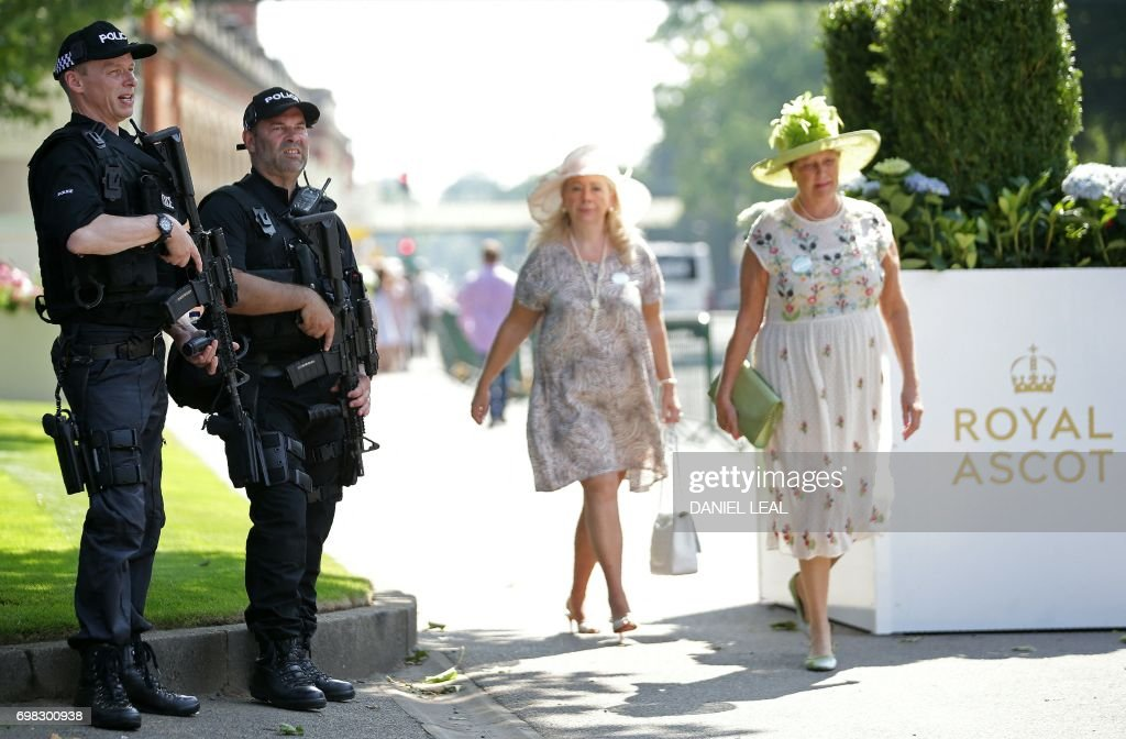 Armed police officers stand on duty as racegoers arrive on day one of the Royal Ascot horse racing meet, in Ascot, west of London, on June 20, 2017. The five-day meeting is one of the highlights of the horse racing calendar. Horse racing has been held at the famous Berkshire course since 1711 and tradition is a hallmark of the meeting. Top hats and tails remain compulsory in parts of the course while a daily procession of horse-drawn carriages brings the Queen to the course. / AFP PHOTO / Daniel LEAL