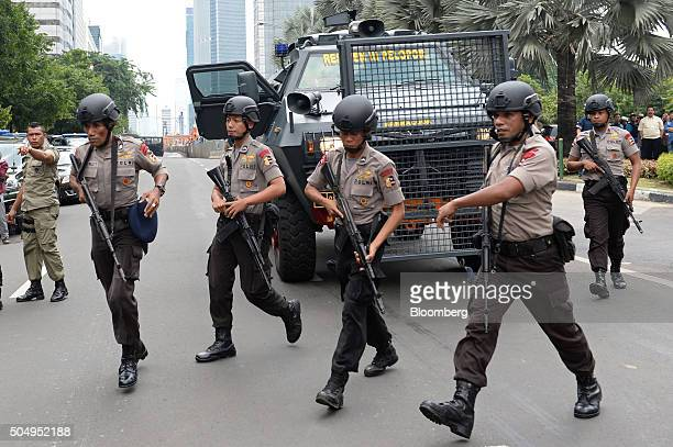 Armed police officers walk past an armored vehicle near the site of an explosion in Jakarta Indonesia on Thursday Jan 14 2016 Explosions ripped...