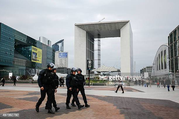 Armed police officers walk through the La Defense business district in front of the Grande Arche in Paris France on Monday Nov 16 2015 Parisians...