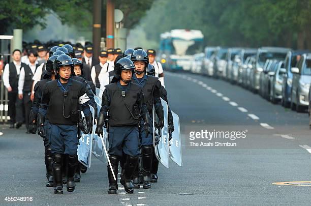 Armed Police officers walk toward the house of Kudokai leader Satoru Nomura on September 11 2014 in Kitakyushu Fukuoka Japan Police arrested the...