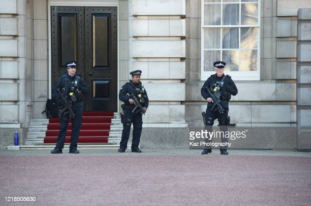 Armed police officers with rifles stand guard at Buckingham Palace amid the coronavirus pandemic on March 25, 2020 in London, England. The...