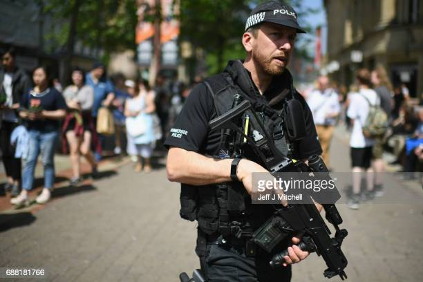 Armed police patrol as members of the public queue to lay flowers in St Ann's Square in memory of those who lost their lives in the Manchester Arena...