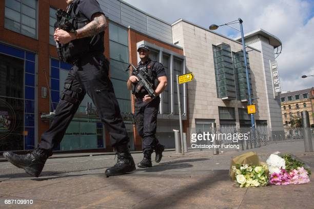 Armed police patrol on Shudehill walking past the first floral tributes to the victims of the terrorist attack on Shudehill May 23 2017 in Manchester...