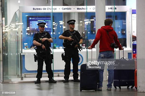 Armed police patrol outside a currency exchange at St Pancras International railway station in London UK on Tuesday March 22 2016 Explosions ripped...