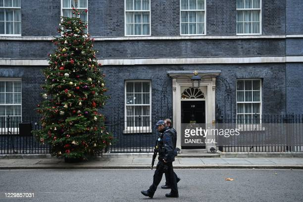 Armed police patrol past the Christmas tree standing beside the front door, outside 10 Downing Street in central London on November 29, 2020.