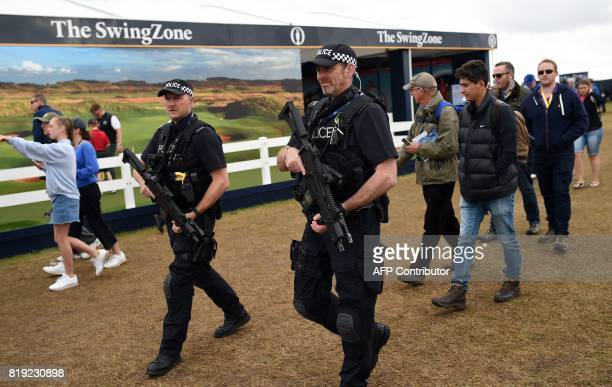 Armed police patrol the course as play gets underway on the first day of the Open Golf Championship at Royal Birkdale golf course near Southport in...