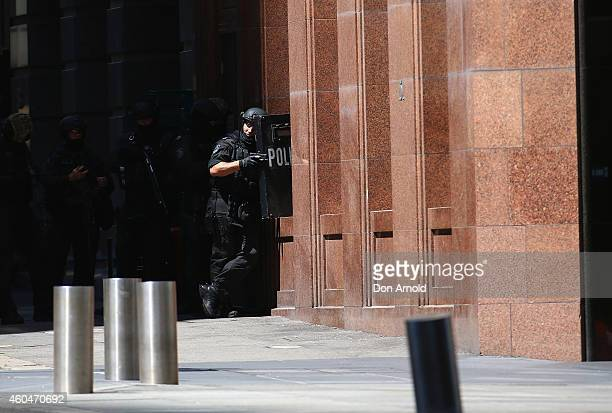 Armed police patrol the vicinity at Lindt Cafe Martin Place on December 15 2014 in Sydney Australia Major landmarks in Sydney including the Sydeny...