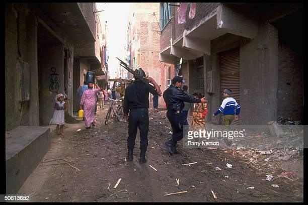 Armed police querying locals in slum condition streets during massive op netting radicals extremists in Muslim fundamentalist stronghold Imbaba