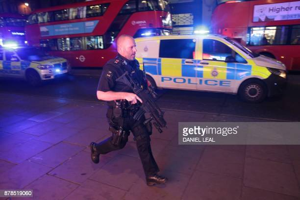 Armed police run along Oxford street as they respond to an incident in central London on November 24 2017 British police said they were responding to...