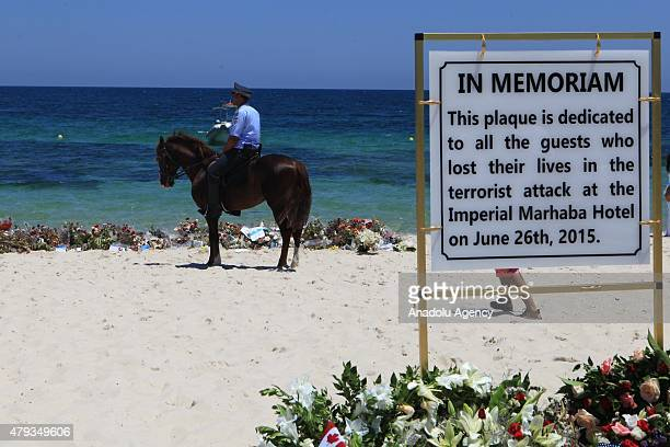 Armed police stand alongside tourists during a remembrance ceremony for the victims of a terror attack on a beach outside the Imperial Marhaba Hotel...