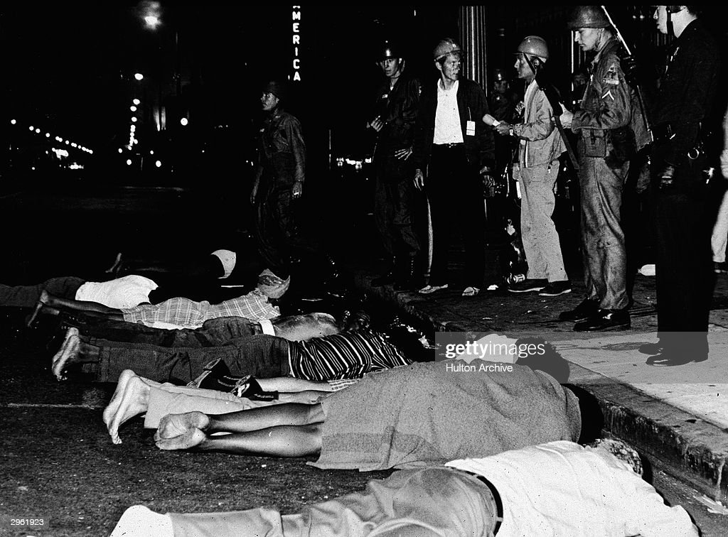 Armed police stand by as rioters lay face down in the street during the Watts race riots, Los Angeles, California, August 1965.