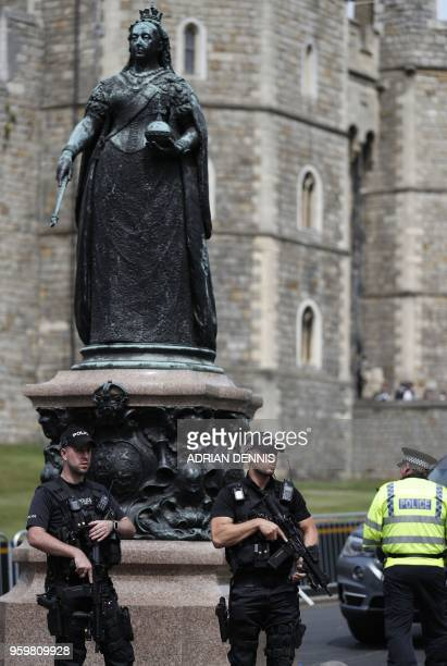 Armed police stand guard beside the Statue of Queen Victoria in Windsor on May 18 the day before the Royal wedding Britain's Prince Harry and US...