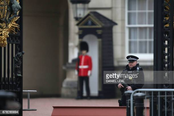 Armed police stand guard outside Buckingham Palace in central London on May 4 2017 There is 'no cause for alarm' over the health of Queen Elizabeth...