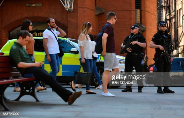 Armed police stand guard to secure the area around Albert Square during the GreatCity Games in central Manchester northwest England on May 26 2017...