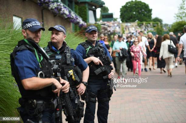 Armed police stand on St Mary's Walk as spectators stream past at The All England Lawn Tennis Club in Wimbledon southwest London on July 3 2017 on...