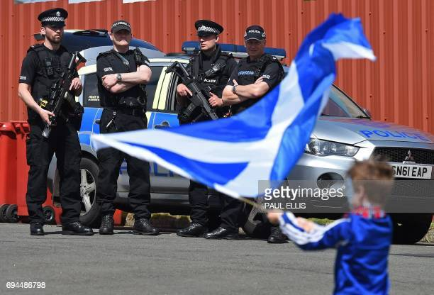 Armed police stand ready as a young Scotland fan waves The Saltire the Scottish flag ahead of the group F World Cup qualifying football match between...