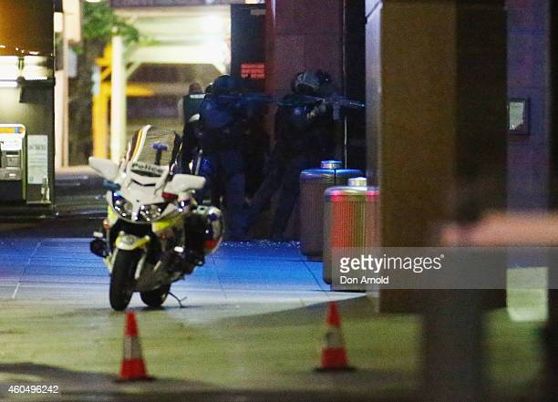 Armed police take aim outside the Lindt Cafe Martin Place on December 15 2014 in Sydney Australia Police attend a hostage situation at Lindt Cafe in...