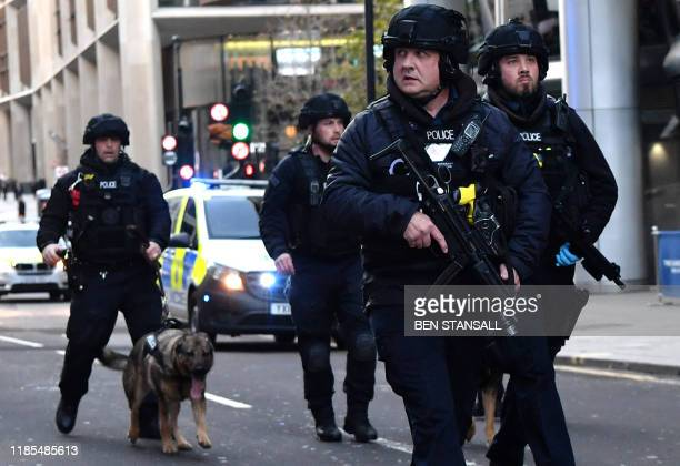 TOPSHOT Armed police with dogs patrol along Cannon Street in central London on November 29 2019 after reports of shots being fired on London Bridge...