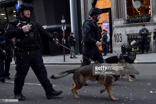 Armed police with dogs patrol along Cannon Street in central London, on November 29, 2019 after reports of shots being fired on London Bridge. - The...