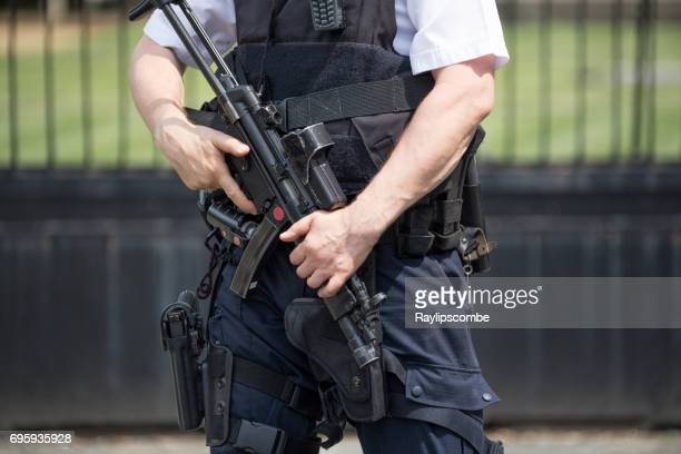Armed policeman standing guard outside the Houses of Parliament, Westminster, London England