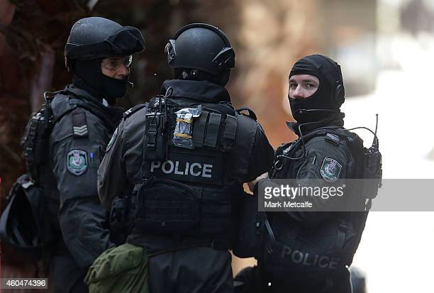 Armed policeman talk on Phillip St close to Martin Place on December 15 2014 in Sydney Australia Police attend a hostage situation at Lindt Cafe in...