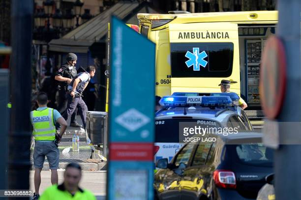 Armed policemen arrive in a cordoned off area after a van ploughed into the crowd injuring several persons on the Rambla in Barcelona on August 17...