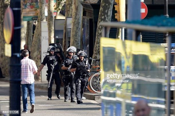 Armed policemen arrive in a cordoned off area after a van ploughed into the crowd killing one person and injuring several others on the Rambla in...
