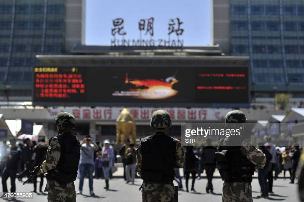 Armed policemen stand guard on the square outside the railway station in Kunming, southwest China's Yunnan province on March 2, 2014. Knife-wielding...