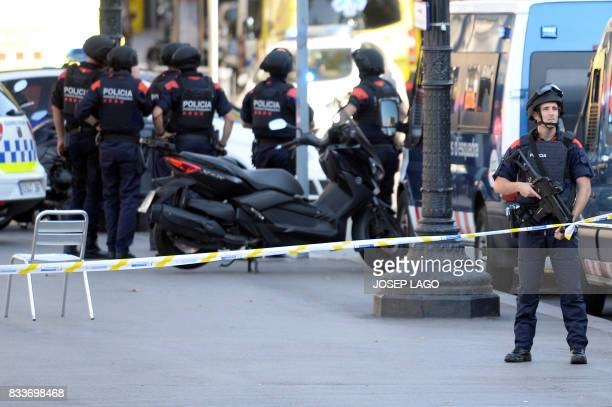 TOPSHOT Armed policemen stand in a cordoned off area after a van ploughed into the crowd injuring several persons on the Rambla in Barcelona on...