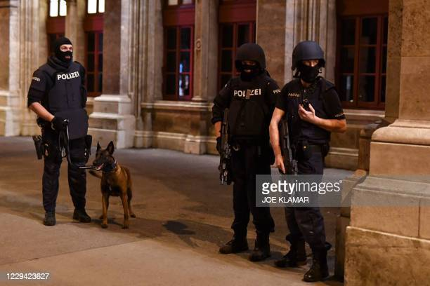 Armed policemen stand witha a dog near the State Opera in the center of Vienna on November 2 following a shooting near a synagogue. - Multiple...