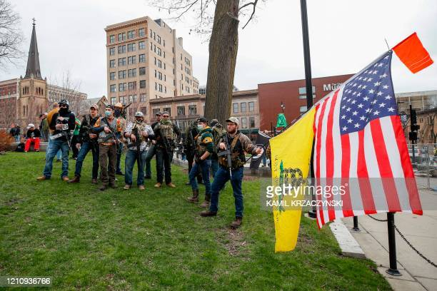 Armed protesters pose for a photo during a demonstration against the coronavirus shutdown in front of the State Capitol in Madison Wisconsin on April...