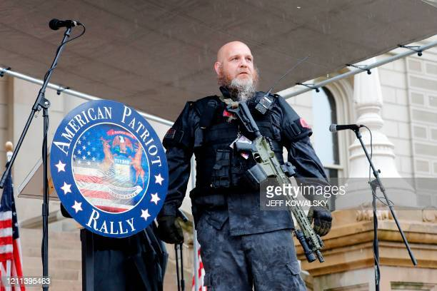 Armed protesters provide security as demonstrators take part in an American Patriot Rally organized on April 30 by Michigan United for Liberty on the...