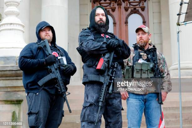 "Armed protesters provide security as demonstrators take part in an ""American Patriot Rally,"" organized on April 30 by Michigan United for Liberty on..."