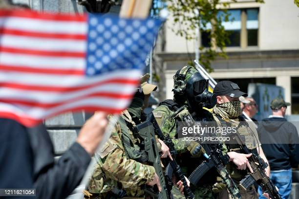 Armed protesters rally outside the New Hampshire State House calling for Governor Chris Sununu to open the state in Concord on May 2 2002 According...