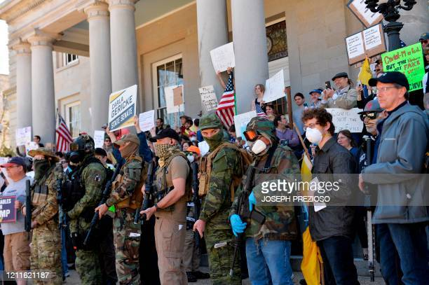 TOPSHOT Armed protesters rally outside the New Hampshire State House calling for Governor Chris Sununu to open the state in Concord on May 2 2002...