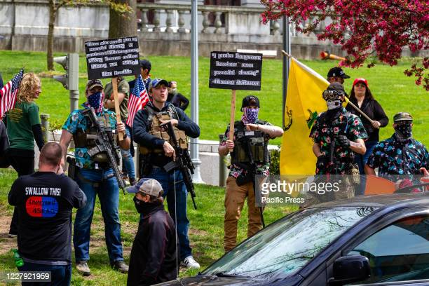 Armed protesters stand in front of the Pennsylvania State Capitol during the Reopen PA Rally. Protesters gathered at the Capitol to demand that...