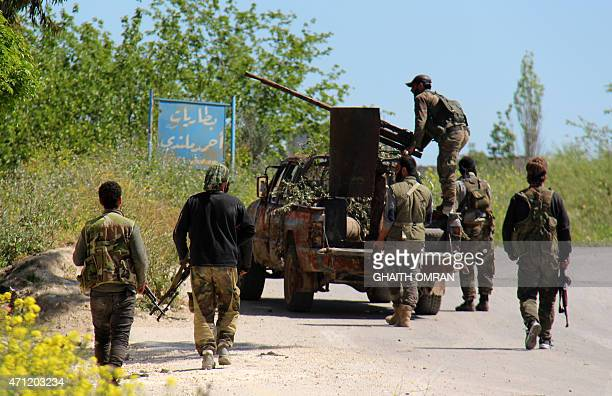 Armed rebel fighters walk down a road in the northern Syrian town of Jisr alShughur on April 25 2015 AlQaeda's Syrian affiliate and other Islamist...