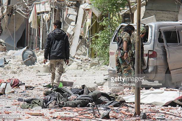 Armed rebel fighters walk past bodies reportedly belonging to government forces in the northern Syrian town of Jisr alShughur on April 25 2015...