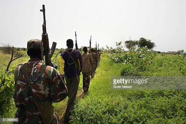 Armed rebel Sudanese Justice and Equality Movement fighters march in colum through the bush towards their base in the Darfur region of Sudan on...