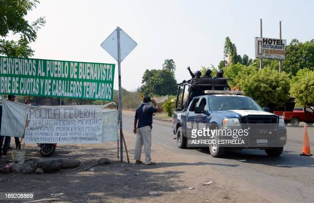 Armed residents members of a vigilante group wave to Federal Policemen at a check point at the entrance of Buenavista Tomatlan during an operation to...
