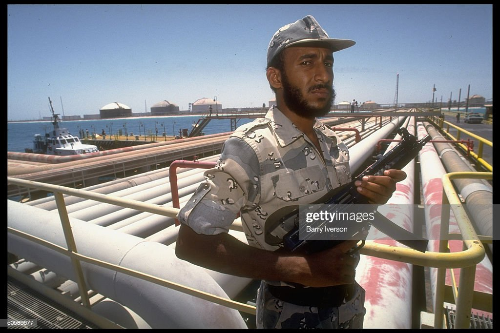 Armed security guard (on gulf crisis alert) poised by pipelines & port facilties at Saudi Aramco oil refinery & loading terminal at Ras Tanura, Saudi Arabia.