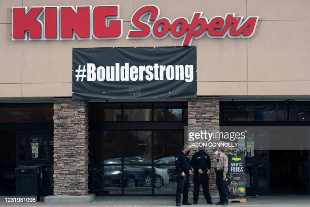 """Armed security guards stand below a sign reading """"#Boulderstrong"""" outside of a King Soopers grocery store in Boulder, Colorado on March 25 days after..."""