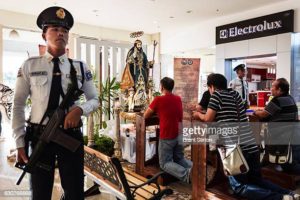 Armed security guards watch over an ivory carved St Joseph statue on display at a religious exhibit in Park Mall shopping center Cebu Philippines...