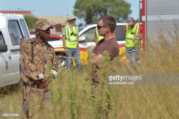 Armed security men stand guard as rescuing operations go underway at an illegal gold mine in Benoni outside Johannesburg on February 16 2014 Eleven...