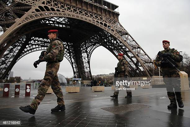 Armed security patrols around the Eiffel Tower on January 9 2015 in Paris France A huge manhunt for the two suspected gunmen in Wednesday's deadly...