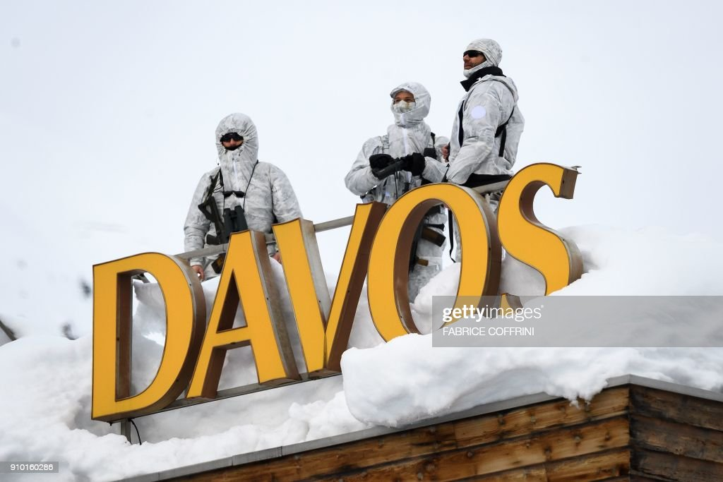 Armed security personnel stand guard on the rooftop of a hotel, next to letters reading 'Davos' surrounded by snow, near the Congress Centre on January 25, 2018 in Davos, eastern Switzerland. / AFP PHOTO / Fabrice COFFRINI