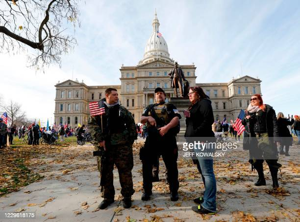 Armed security watch as people gather in support of US President Donald Trump at the Michigan State Capitol, on November 14, 2020 in Lansing,...