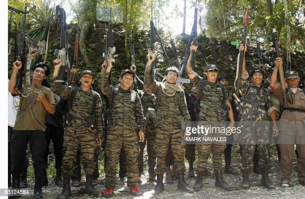 Armed separatist Muslim guerrillas of the Moro Islamic Liberation Front raise their rifles after they declared red alert status around Camp...